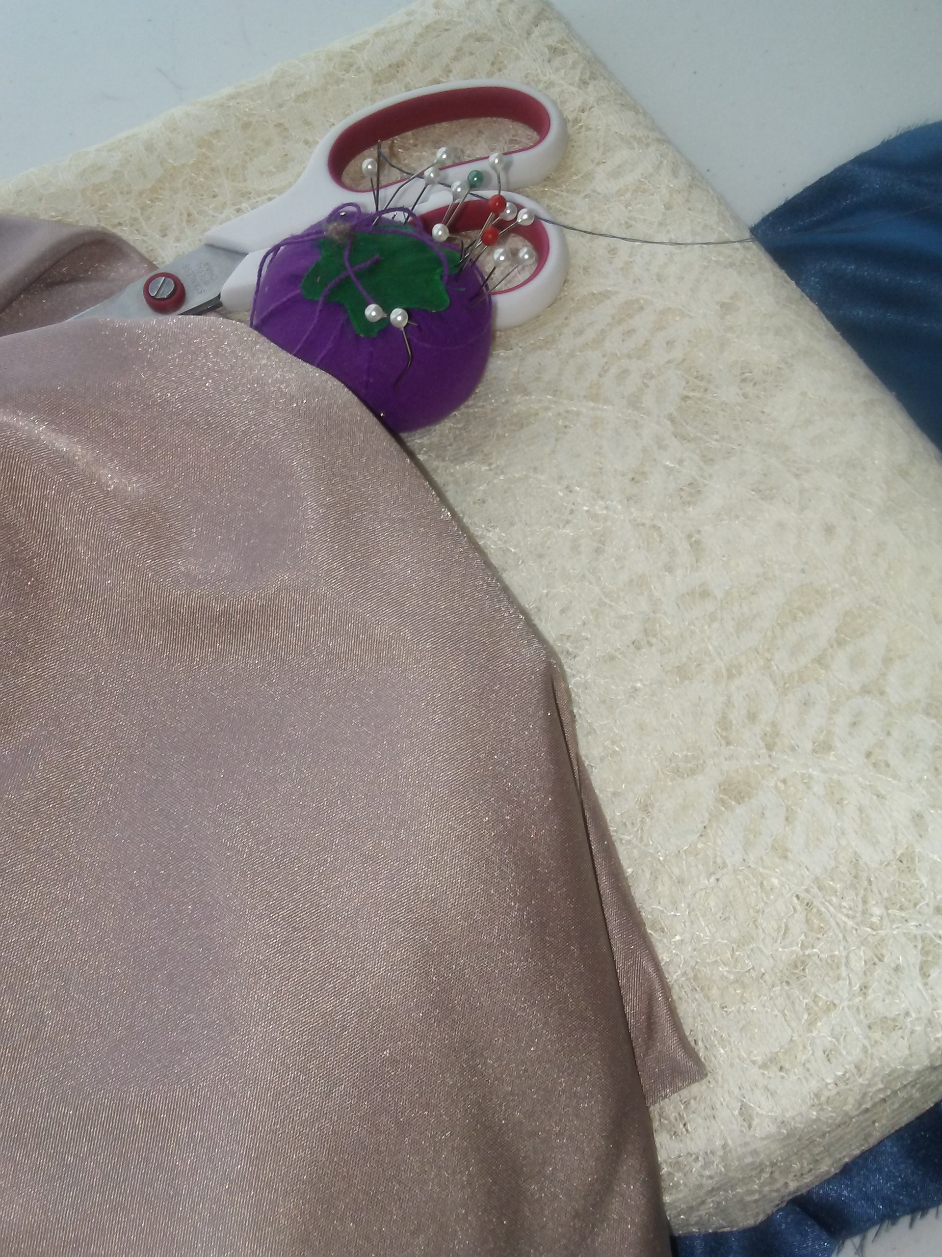 photo of purple fabric and a white lace fabric with a pair of scissors and a pin cushion.